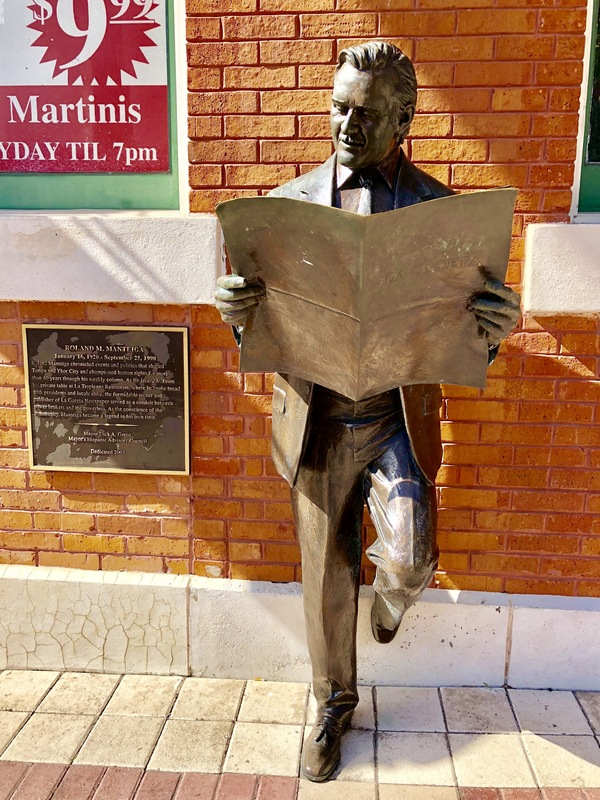 Statue of Roland Manteiga leaning against the Centro Espanol building reading a La Gaceta newspaper, situated on 7th Ave in Ybor City